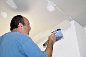 a handyman muds a newly installed drywall ceiling panel